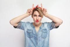 Portret van grappige mooie jonge vrouw in toevallig blauw denimoverhemd met make-up en rode hoofdband die zich met hoornenhanden  royalty-vrije stock fotografie