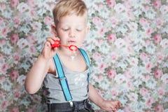 Portret van grappige weinig jongens blazende zeepbels (Portret van grappige weinig jongens blazende zeepbels. Achtergrond: bloemen Stock Afbeelding