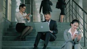 Portret van groep bedrijfsmensen die aan hun gadgets werken die op de treden zitten stock videobeelden