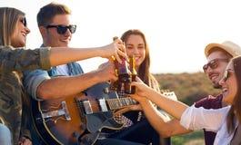 Portret van groep vrienden die met flessen bier roosteren Royalty-vrije Stock Foto
