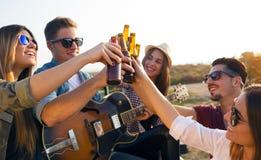 Portret van groep vrienden die met flessen bier roosteren Stock Afbeelding