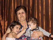 Portret van grootmoeder met twee kleinkinderen stock afbeeldingen