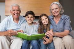 Portret van grootouders en grandkids het bekijken albumfoto Stock Afbeelding