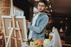 Portret van Guy Painting op Schildersezelstilleven stock fotografie