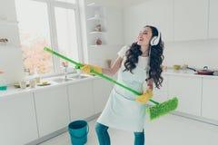 Portret van haar zij aardige leuke mooie mooie vrolijke positieve wavy-haired huisvrouw die bezem gebruiken die hebbend pret dans stock afbeelding