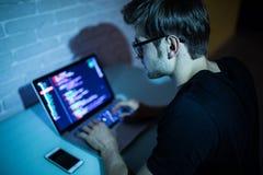 Portret van hakker met laptop op donkere achtergrond in de nacht Royalty-vrije Stock Afbeelding