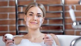 Portret van het aanbiddelijke het glimlachen jonge vrouw stellen met masker op gezicht die bad nemen die camera bekijken stock footage