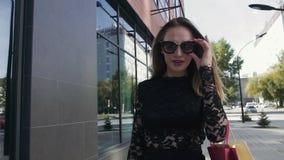 Portret van het aantrekkelijke blonde vrouw lopen op een zonnige dag na het winkelen stock footage