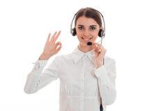 Portret van het aantrekkelijke donkerbruine die meisje van de call centrearbeider met hoofdtelefoons en microfoon op witte achter Stock Foto's