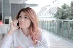 Portret van het aantrekkelijke jonge Aziatische bedrijfsvrouw spreken op telefoon voor haar baan in bureau met exemplaar ruimteac Stock Afbeeldingen