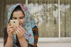 Portret van het Aantrekkelijke Leuke Moslimmeisje Werken met Slimme Telefoon Royalty-vrije Stock Fotografie