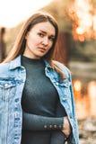Portret van het aantrekkelijke, slanke, mooie jonge Kaukasische blondemeisje in een jeansjasje Het glimlachende meisje geniet van royalty-vrije stock foto's