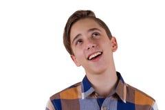 Portret van het aantrekkelijke tienerjongen glimlachen en het kijken omhoog wordt gefotografeerd in een studio Geïsoleerdj op wit stock foto