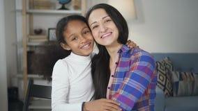 Portret van het Afrikaanse Amerikaanse jonge meisje spreken en het lachen met haar volwassen schoolleraar die in camera kijken stock footage