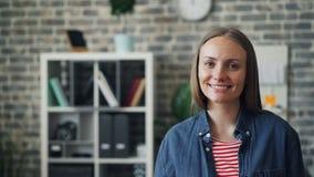 Portret van het blije jonge dame glimlachen die camera bekijken die zich in werkplaats bevinden stock video