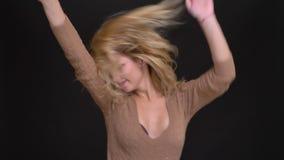Portret van het blije Kaukasische langharige vrouw dansen vreemd in camera op zwarte achtergrond stock footage