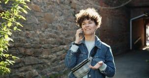 Portret van het blije meisje spreken op mobiele telefoon in openlucht in straat het glimlachen stock videobeelden