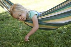 Portret van het blonde kindmeisje ontspannen op een kleurrijke hangmat Royalty-vrije Stock Foto's