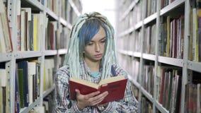 Portret van het charmante vrouwelijke boek van de studentenlezing in universitaire bibliotheek stock footage
