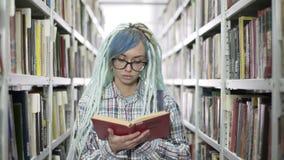 Portret van het charmeren van jonge vrouw die een boek in bibliotheek lezen stock video