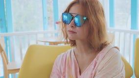 Portret van het charmeren van jonge vrouw in zonnebril binnen in langzame motie stock video