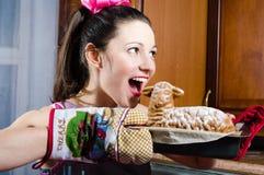 Portret van het charmeren van grappige donkerbruine jonge dame in handschoenen die pret gelukkige het glimlachen het bijten smake stock foto's