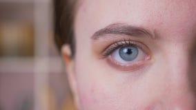 Portret van het close-up het halve gezicht van jong aantrekkelijk Kaukasisch wijfje die met ogen camera bekijken stock footage