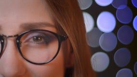 Portret van het close-up het halve gezicht van jong vrij Kaukasisch meisje in glazen die camera bekijken en gelukkig met bokeh gl stock video