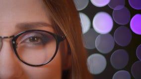 Portret van het close-up het halve gezicht van jong vrij Kaukasisch meisje in glazen die camera bekijken en met bokehachtergrond  stock footage