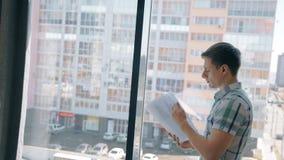 Portret van het contract van de zakenmanlezing dichtbij het venster stock videobeelden