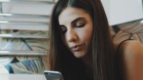 Portret van het donkerbruine jonge meisje spreken op telefoon in badkamers Maak omhoog stock videobeelden