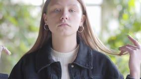 Portret van het droevige tienermeisje kijken in camera wat betreft haar haar dicht omhoog De jonge vrouw neemt haar vingers het h stock videobeelden