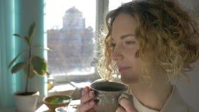 Portret van het dromen van meisje die hete koffie van kopclose-up drinken tegen zonovergoten venster stock footage