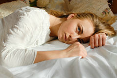 Portret van het emotionele mooie blonde jonge dame ontspannen die in bed liggen die exemplaarruimte bekijken op slaapkamer achter Royalty-vrije Stock Fotografie