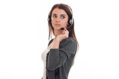 Portret van het ernstige donkerbruine die meisje van de call centrearbeider met hoofdtelefoons en microfoon op witte achtergrond  Stock Afbeeldingen