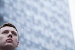 Portret van het ernstige jonge zakenman omhoog kijken, in openlucht, bedrijfsdistrict Stock Afbeeldingen