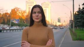 Portret van het ernstige Kaukasische donkerbruine letten bescheiden op in camera met haar die wapens op wegachtergrond worden gek stock footage