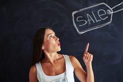 Portret van het geïnspireerde vrouw richten op het getrokken verkoopetiket Stock Fotografie