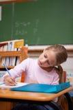 Portret van het geconcentreerde schoolmeisje schrijven Stock Foto