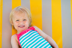 Portret van het gelukkige baby leggen op zonbed Royalty-vrije Stock Foto's
