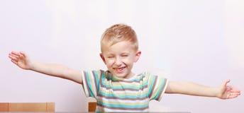 Portret van het gelukkige blonde jonge geitje van het jongenskind met wapens open bij de lijst Stock Foto