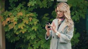 Portret van het gelukkige Blondevrouw kopen online met slimme telefoon in openlucht stock videobeelden