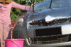 Portret van het gelukkige de auto van hijabvrouwen schoonmaken die - de zeep met water verwijderen, die een tuinslang en een spui royalty-vrije stock afbeeldingen