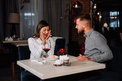 Portret van het gelukkige en verraste jonge vrouw ontvangen huidig van vriend terwijl het zitten in koffie stock foto