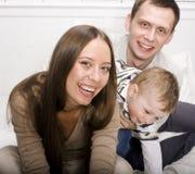 Portret van het gelukkige familie, mamma en papa spelen met hun zoon in bed Stock Foto's