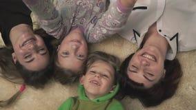 Portret van het gelukkige glimlachende familie en het golven liggen op een pluizig tapijt op de vloer Vrolijke familievakantie stock footage