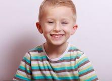 Portret van het gelukkige het lachen blonde jonge geitje van het jongenskind bij de lijst Royalty-vrije Stock Afbeeldingen
