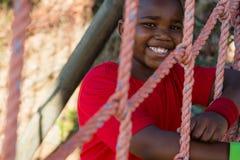 Portret van het gelukkige jongen leunen op netto tijdens hinderniscursus stock fotografie
