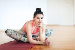 Portret van het gelukkige vrouw donkerbruine sportieve kijken zitting op een deken voor een training Royalty-vrije Stock Afbeeldingen