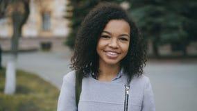 Portret van het gemengde het meisje van de ras krullende student glimlachen in camera en het lachen bij stadsstraat royalty-vrije stock foto's